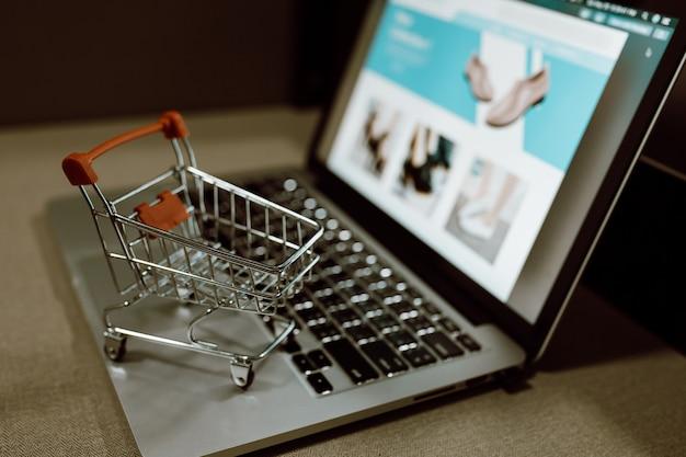 Trolley winkelwagentje op een laptop toetsenbord. ideeën voor online winkelen of e-commerce via internet.