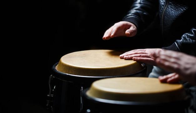 Trommel. handen van een muzikant die op waterpijpen speelt. de muzikant speelt de bongo.