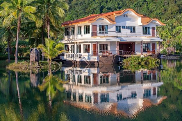 Tropenhuis in de vorm van een schip in een grote lagune met groene palmbomen