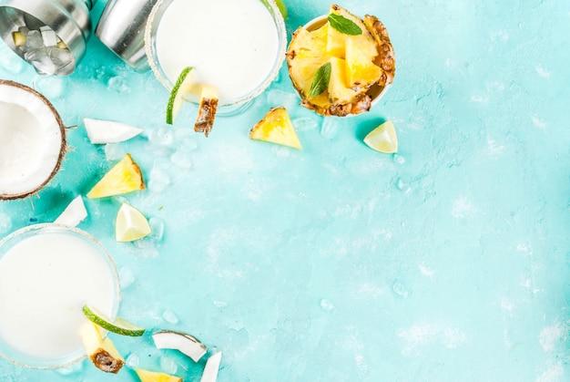 Tropisch drankje frozen coconut ananas margaritas met bevroren pina colada tequila ananassap en limoen lichtblauwe achtergrond