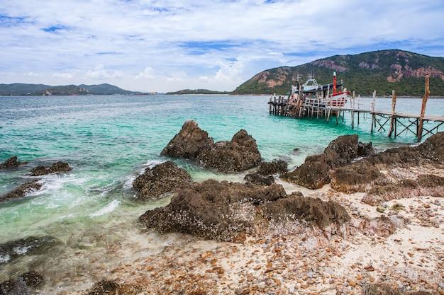 Tropisch eiland met rotsachtig strand en houten brug