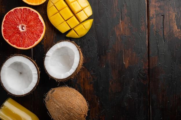 Tropisch fruit, ananas, mango en sinaasappels set, op oude donkere houten tafel achtergrond, bovenaanzicht plat lag, met kopieerruimte voor tekst