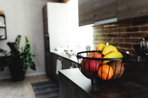 Tropisch fruit: gebroken kokosnoot, appel, mandarijn, sinaasappel, banaan in fruitschaal op toog in stijlvolle zolderkeuken.