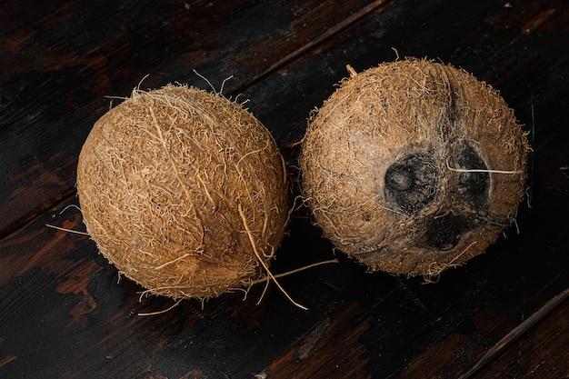 Tropisch fruit kokosnoot hele set, op oude donkere houten tafel achtergrond