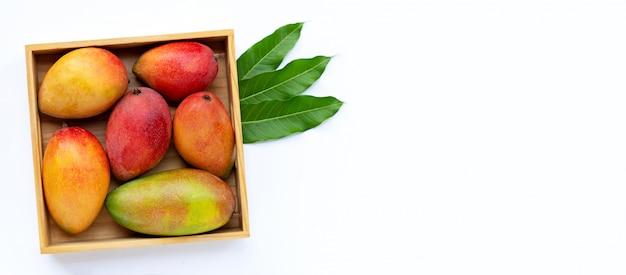 Tropisch fruit, mango in houten doos op witte achtergrond.