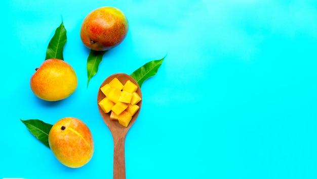 Tropisch fruit, mango op blauwe achtergrond. bovenaanzicht