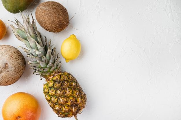 Tropisch fruit set, op witte stenen tafel achtergrond, bovenaanzicht plat lag, met kopie ruimte voor tekst