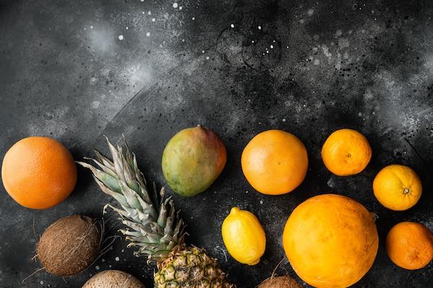 Tropisch fruit set, op zwarte donkere stenen tafel achtergrond, bovenaanzicht plat lag, met kopieerruimte voor tekst