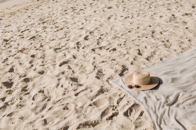 Tropisch mooi strand met wit zand, voetstappen, neutrale deken met strohoed en zonnebril
