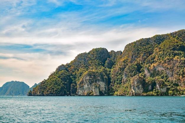 Tropisch rotsachtig eiland in de andaman zee phi phi island kalm blauw water en licht bewolkte lucht