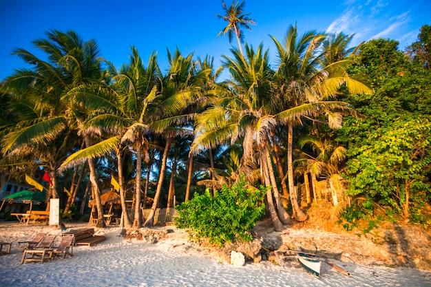 Tropisch strand bij zonsondergang op een exotisch eiland
