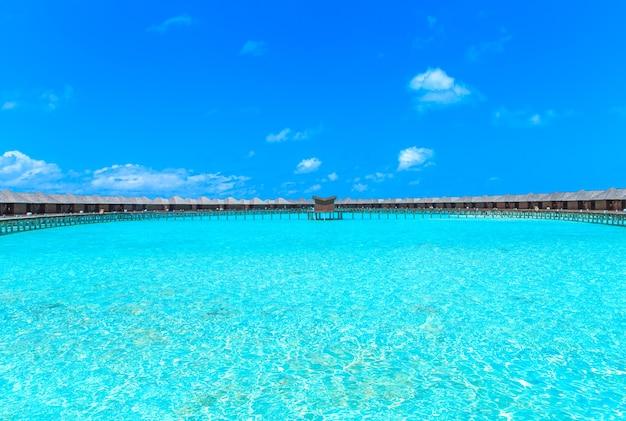 Tropisch strand in de maldiven met enkele palmbomen en blauwe lagune