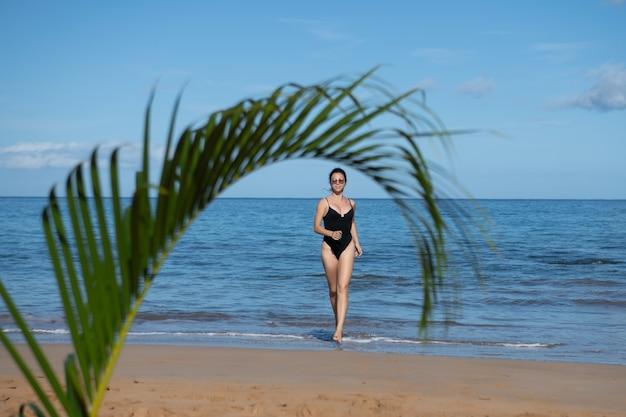 Tropisch strand. jonge gelukkige vrouw die blootsvoets op het strand loopt. zomer strand en zee.