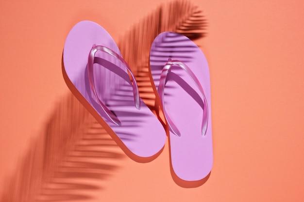 Tropisch strand levensstijl. flip flops en schaduw van een palmblad op koraal kleur achtergrond. zomer achtergrond. bovenaanzicht