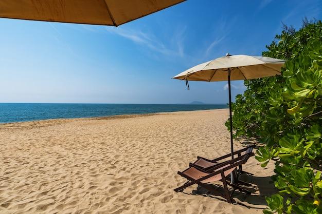 Tropisch strand met parasol onder de palmen in zonlicht, vakantie
