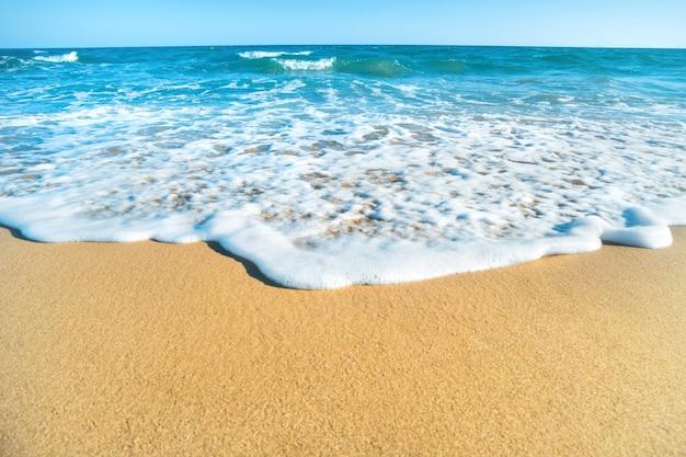 Tropisch strand met zand en zeegolf op de achtergrond