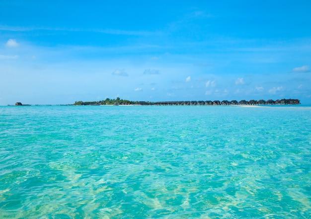 Tropisch strand op de malediven met weinig palmbomen en blauwe lagune