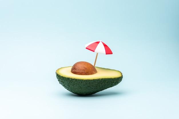 Tropisch strandconcept gemaakt met avocadofruit en parasol