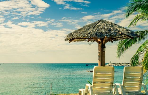 Tropisch strandlandschap met ligstoelen en parasol op zand naast het overzees.