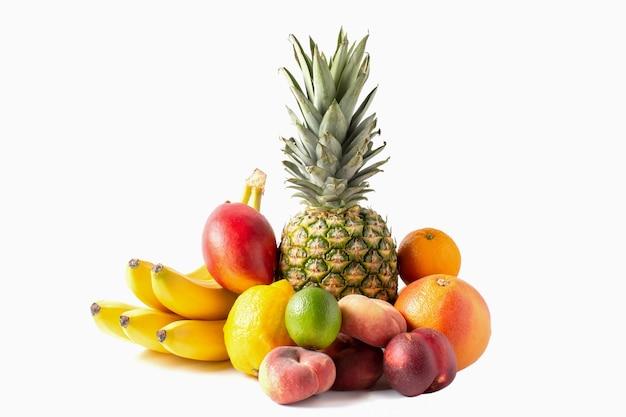 Tropisch vruchten assortiment dat op witte achtergrond wordt geïsoleerd. ananas, bananen, mango, ime, citroen, perziken.