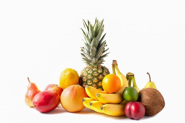 Tropisch vruchten assortiment dat op witte achtergrond wordt geïsoleerd. ananas, kokos, bananen, mango, appel, limoen, citroen, grapefruit en pruim.