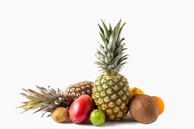 Tropisch vruchten assortiment dat op witte achtergrond wordt geïsoleerd. ananas, kokos, mango, sinaasappel, limoen, citroen en kiwi