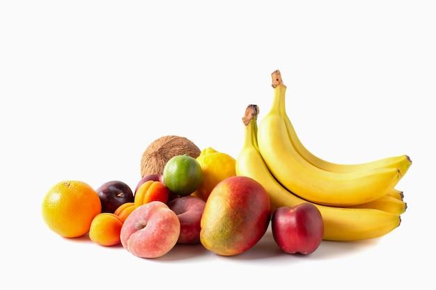 Tropisch vruchten assortiment dat op witte achtergrond wordt geïsoleerd. kokos, bananen, mango, sinaasappel, limoen, citroen, perziken, abrikozen en pruimen.