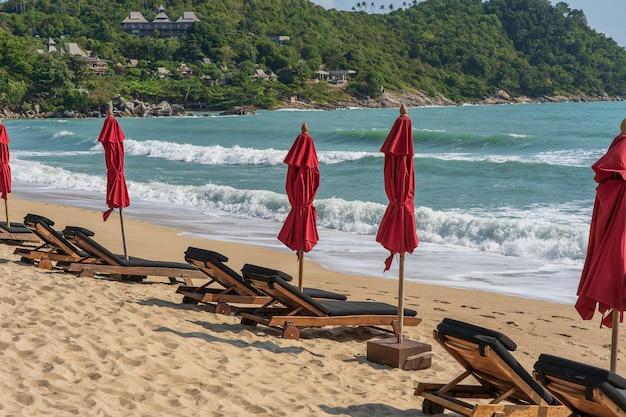 Tropisch zandstrand met houten ligstoelen en rode parasols in de buurt van zee op een zonnige dag. natuurconcept. thailand