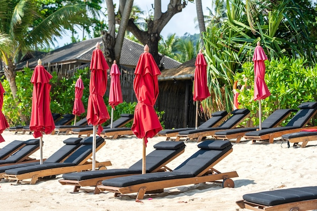 Tropisch zandstrand met houten ligstoelen en rode parasols, op een zonnige dag. natuurconcept. thailand