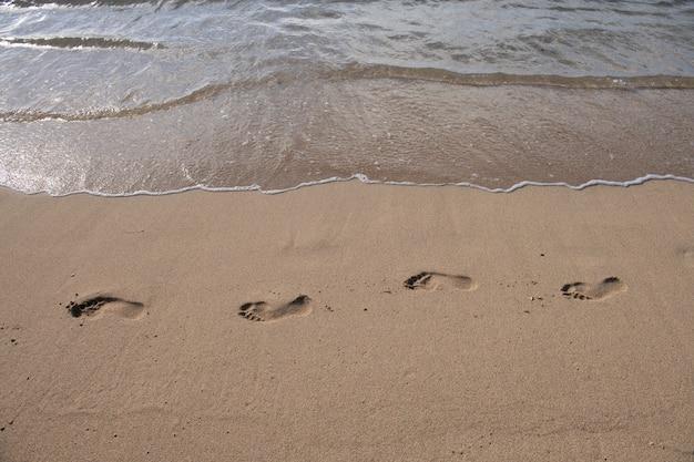 Tropisch zeewater komt op het witte strandzand met voetafdruk.