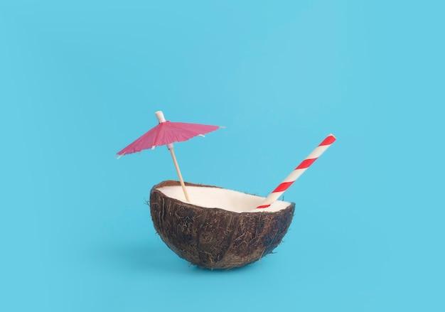 Tropisch zomer- en vakantie minimaal concept. kokosnoot op een blauwe achtergrond met een cocktailstro. vakantie, reizen, strandidee.