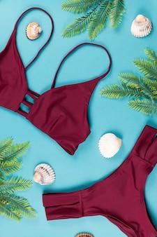 Tropisch zomerconcept met rode bikini, bladeren en schelpen op blauw