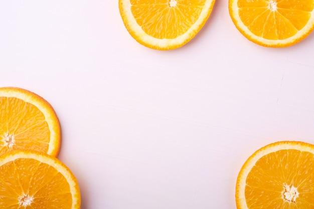 Tropische achtergrond oranje plakjes fruit, bovenaanzicht, kopie ruimte