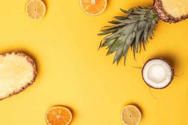 Tropische ananas, sinaasappelen, citroen en kokosnoot op een pastel achtergrond.