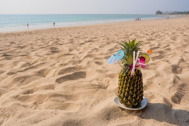 Tropische ananascocktail. verse ananas die op de achtergrond van het zandstrand liggen