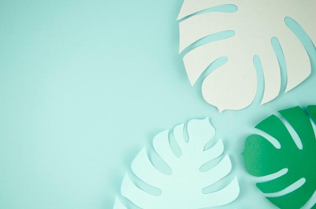 Tropische bladeren in papier gesneden stijl in blauw