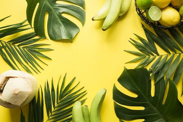 Tropische bladeren, kokosnoot drank en fruit op geel. zomervakantie. ruimte voor tekst.