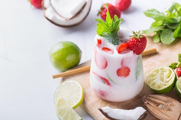 Tropische caraïbische cocktailmojito met kokosroom, aardbei en seltzer