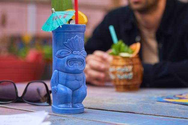 Tropische cocktail met sinaasappel in het blauwe glas van de tiki-stijl op houten achtergrond