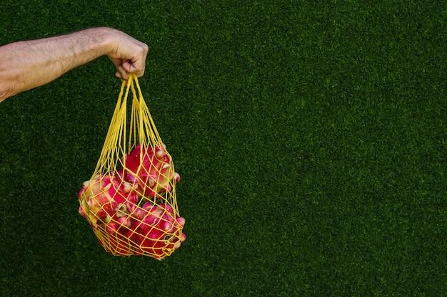 Tropische draakvruchten in geel het winkelen mesh bag op een groene oppervlakte, nul afvalconcept, exemplaarruimte