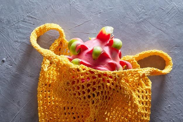 Tropische dragon fruit in een string zak op een grijze betonnen ondergrond. winkelen eten met milieuvriendelijke tas.
