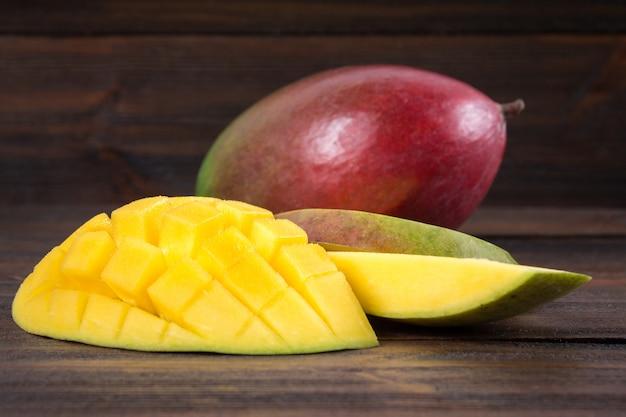 Tropische fruitmango op een houten achtergrond, geheel of gesneden.