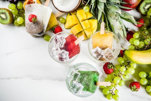 Tropische ijslollys met chiazaad en vruchtensap - ananas, sinaasappel, mango, banaan, kiwi, kokosnoot, druiven, perzik, aardbei