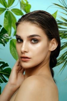 Tropische jungle vrouw met blote schouders lichte make-up schone huid groene bladeren gezondheidszorg
