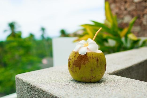 Tropische kokosnoot cocktail versierd plumeria op tafel.