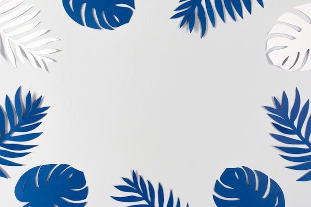Tropische papierbladeren op grijze achtergrond. kleur van het jaar 2020 - classic blue.