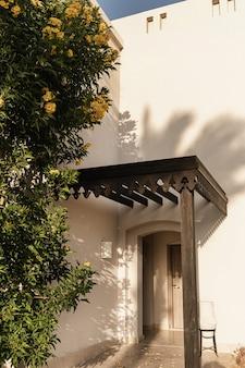 Tropische plant met gele bloemen op beige muur van het huisgebouw