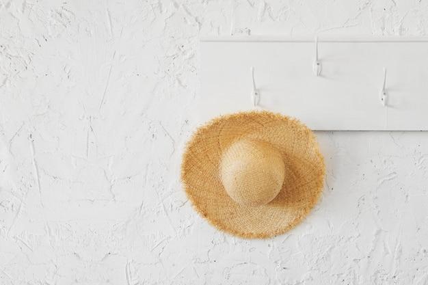 Tropische rieten hoed op een witte houten hanger in een minimalistisch interieur.