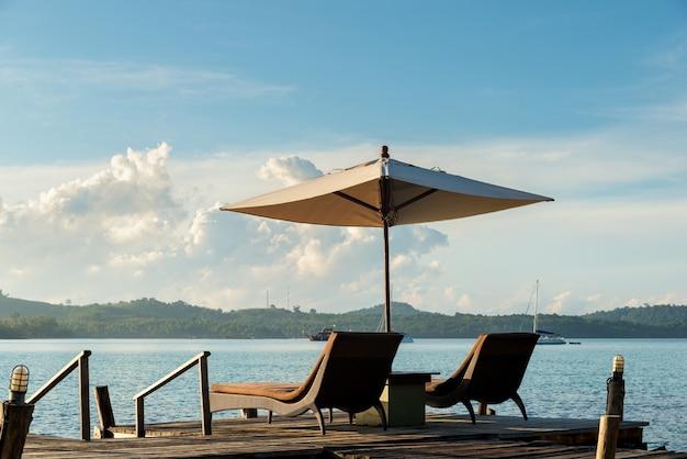 Tropische strandtoevlucht met zitkamerstoelen en paraplu's in phuket, thailand.