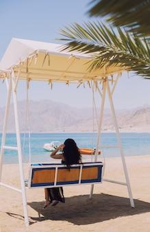 Tropische vakantie achtergrond met palm, zee en meisje op schommelbank